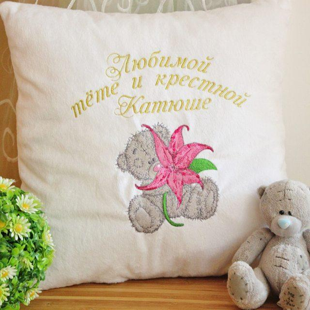 A pillow with a teddy-bear holding a lily embroidery design