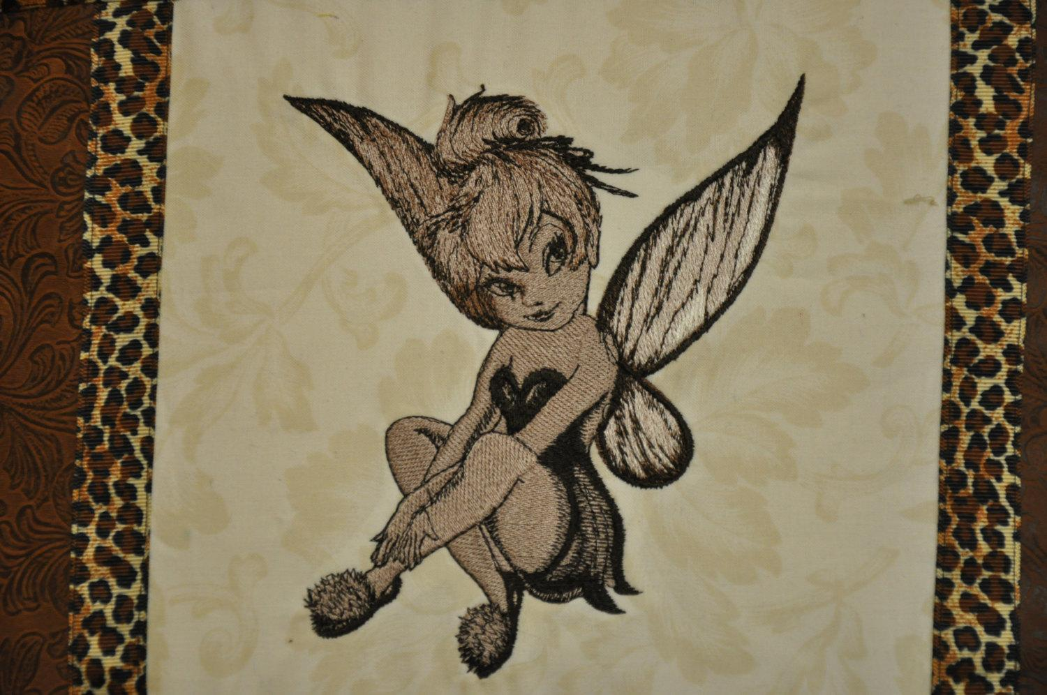 A pillow decorated with Tinker Bell embroidery design