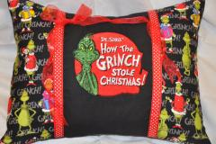 A pillow with Grinch embroidery design