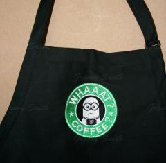 A black apron with a Whaat? Coffee? minion embroidery design