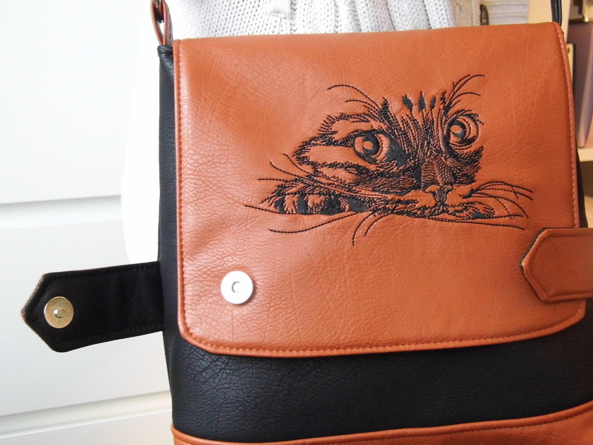 Leather bag with Curious cat machine embroidery design