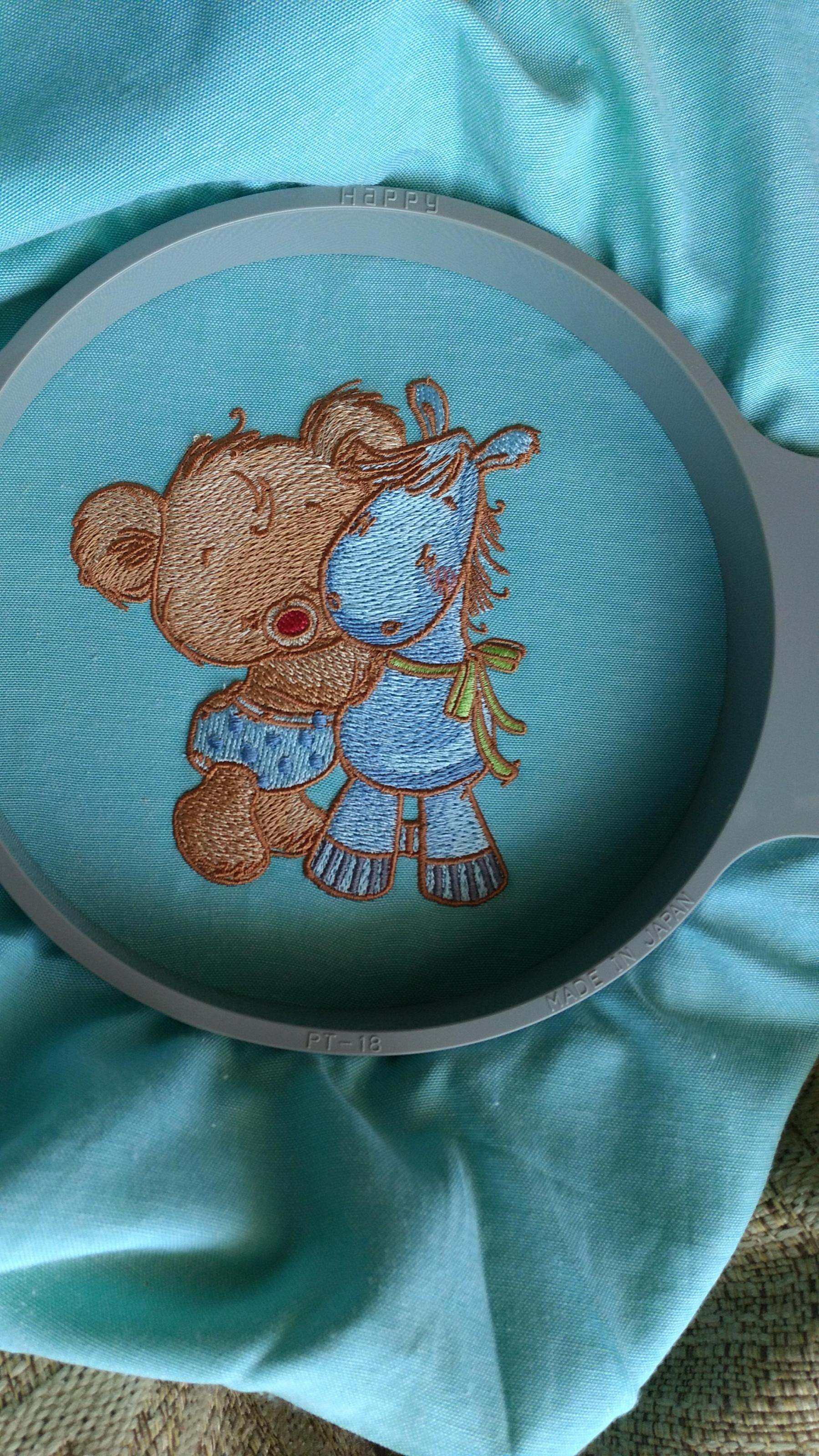Finished teddy and pony embroidered design in round hoop