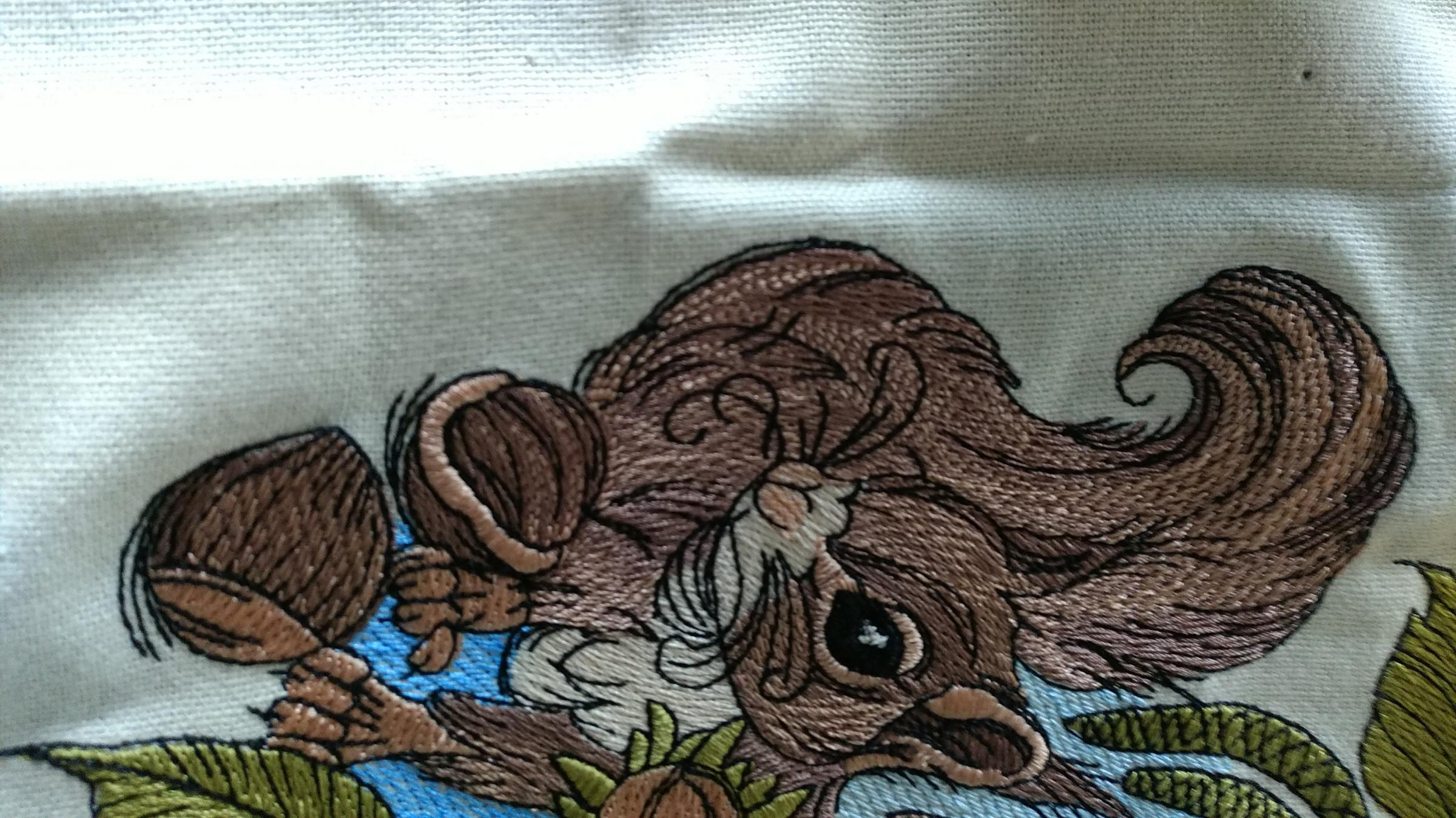 Squirrel with hazelnut embroidery design at napkin
