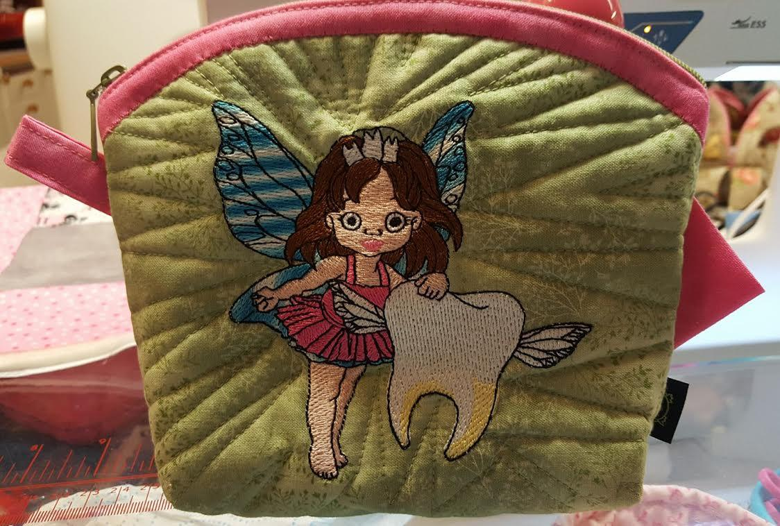 Embroidered handbag with tooth fairy design