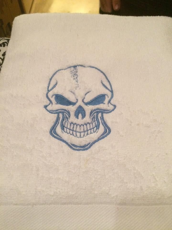 Embroidered towel with smiling skull design