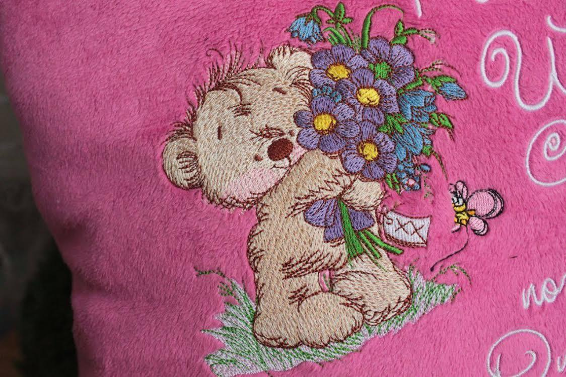 Fragment of embroidered pillow with bear and bouquet design