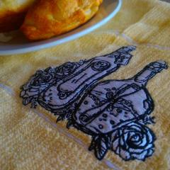 Embroidered napkin with two bottles and flowers design