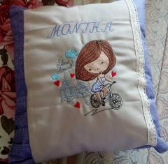 Embroidered pillow with girl on bicycle design