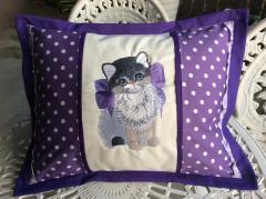 Embroidered pillow with kitty in bow design