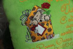 Fragment of embroidered pillow with dog in box design