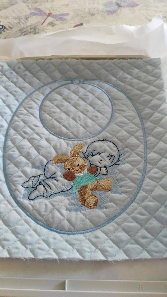 Embroidered bib with baby and toy design