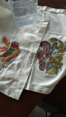 Embroidered napkin with siberian rubythroat and squirrel designs