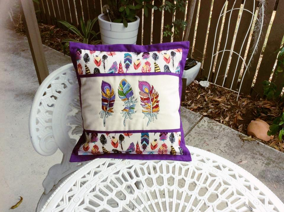 Embroidered cushion with rainbow feathers designs
