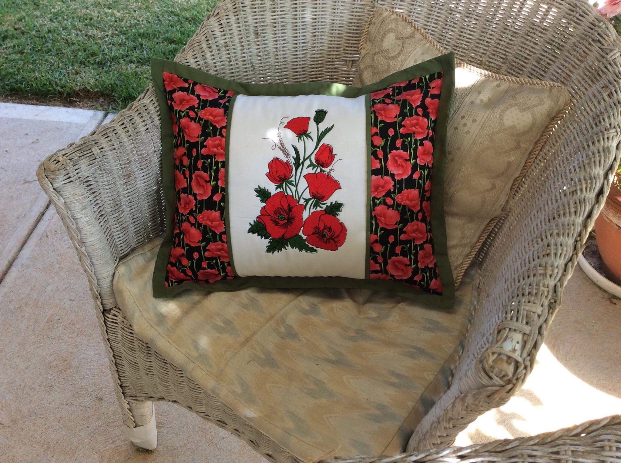 Embroidered cushion with red poppies design