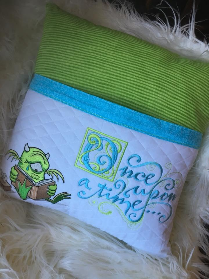Embroidered cushion with reading alien design