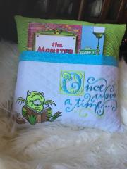 Embroidered pillow with reading alien design