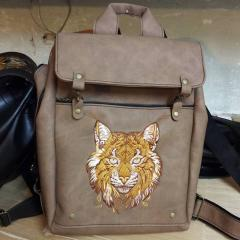 Embroidered leather bag with forest cat design