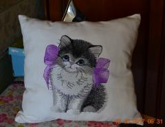 Embroidered cushion with kitten and bow design