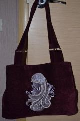 A bag with the head of a mysterious lady embroidered on it
