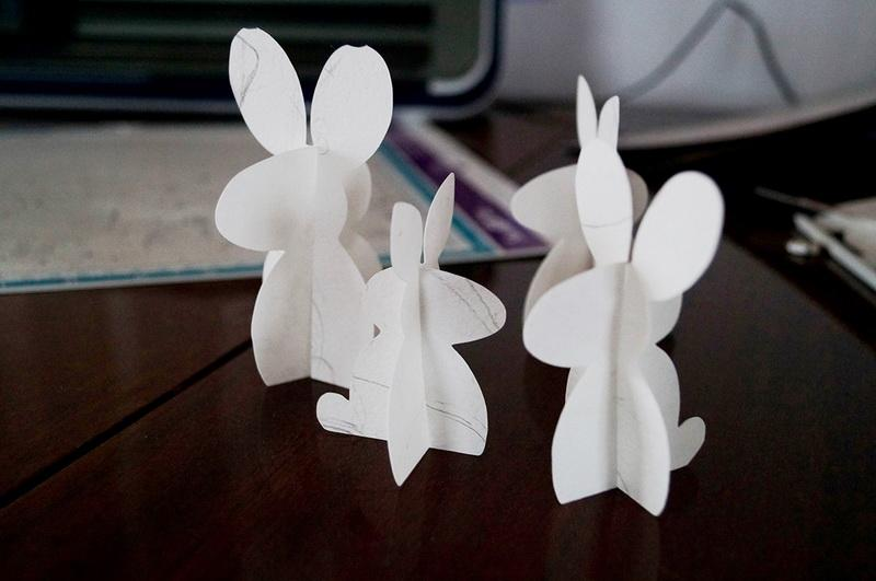Paper Easter bunnies standing on table