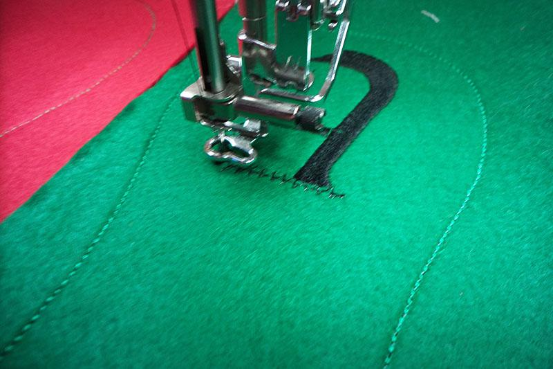 Black letter embroidered on green fabric