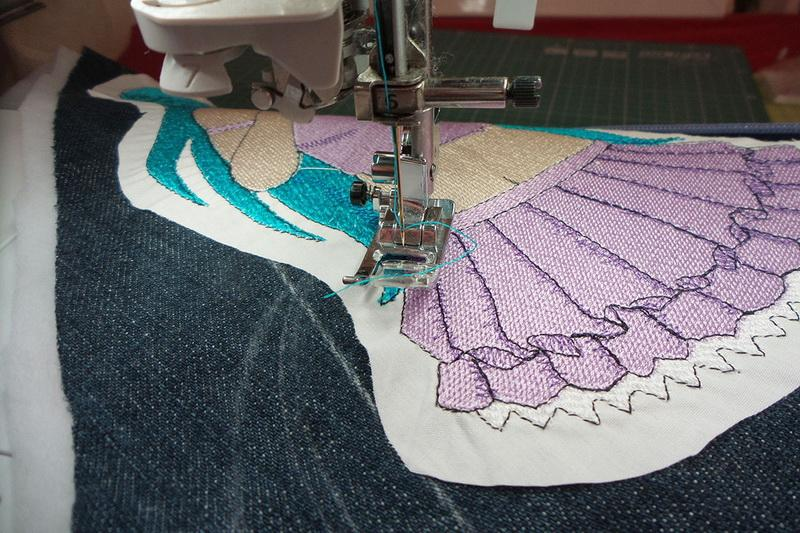 Embroidery design being stitched to denim