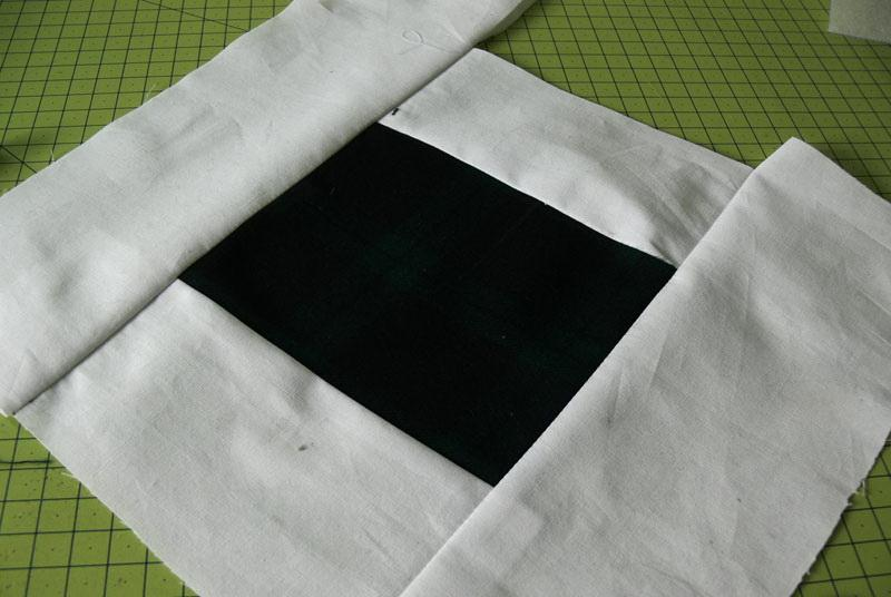 Four strips of white calico stitched to green fabric perimeter-wise