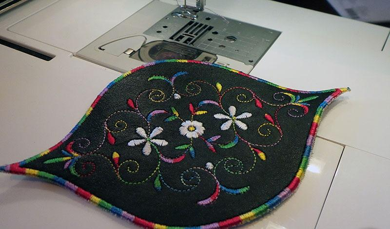 Black leather bracelet lying on embroidery machine