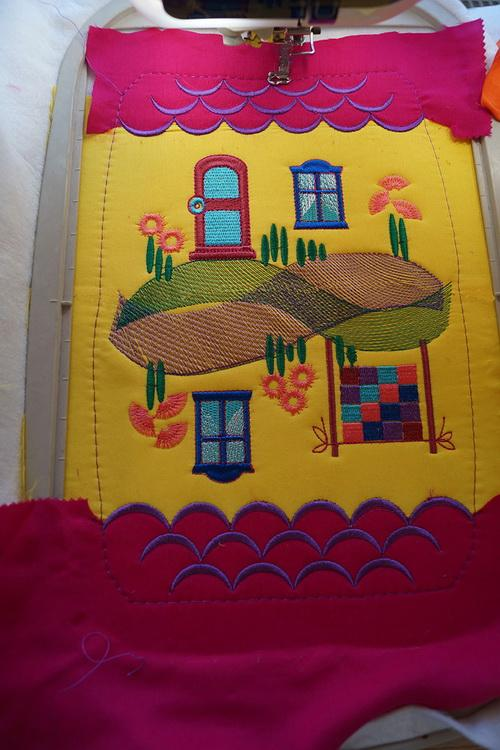 The house embroidered on yellow and red fabric