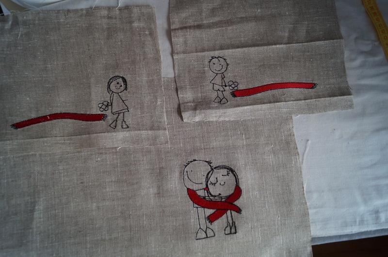 Three pieces of linen with red and black embroidered designs
