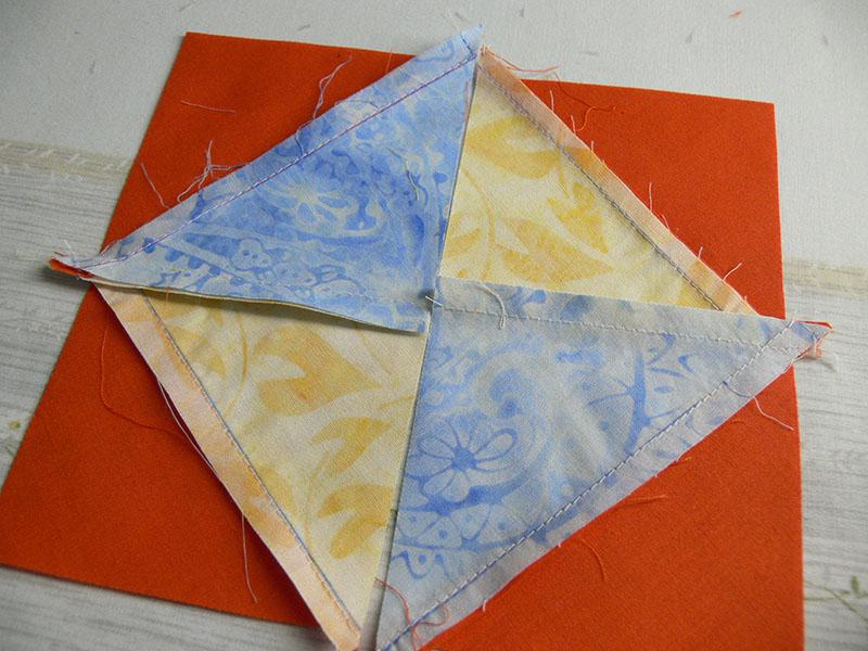 Blue and yellow triangular pieces of fabric arranged into a square