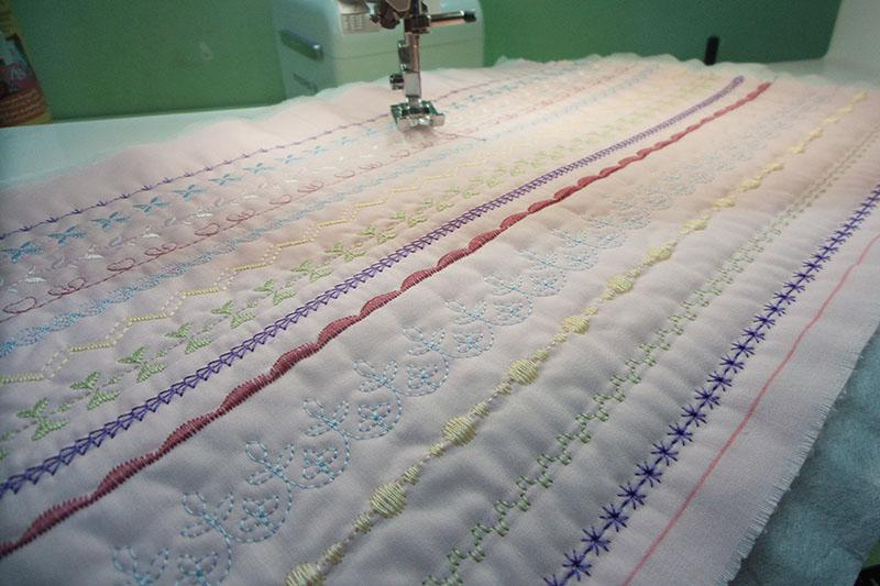 Many-colored stitches on pink fabric