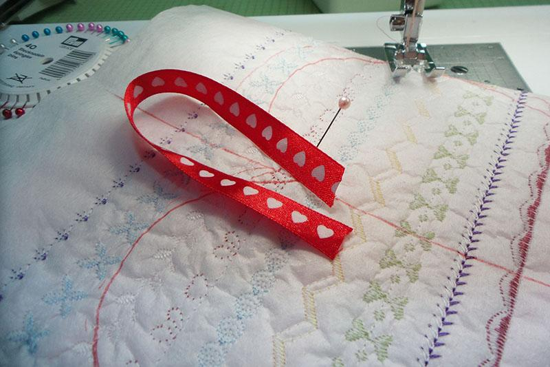 Red ribbon with hearts on pink fabric