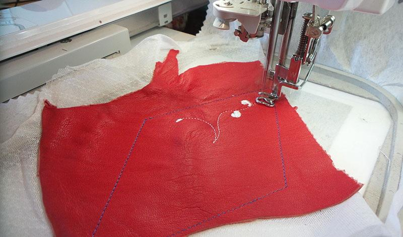 Piece of red leather with part of the design