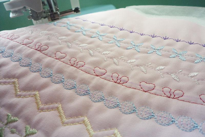 Many-colores stitches on pink fabric: closer look