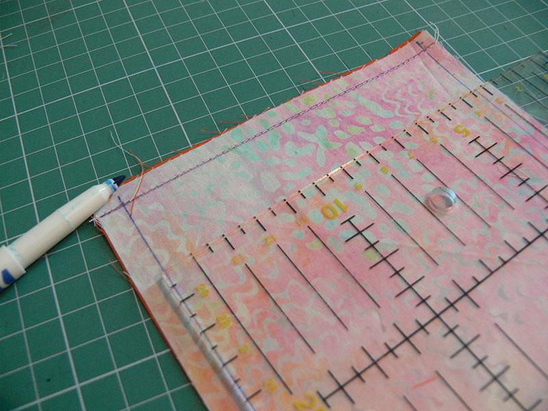 Sewing ruler on piece of fabric with print