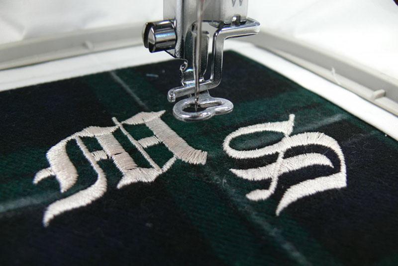 White monograms on green checkered fabric