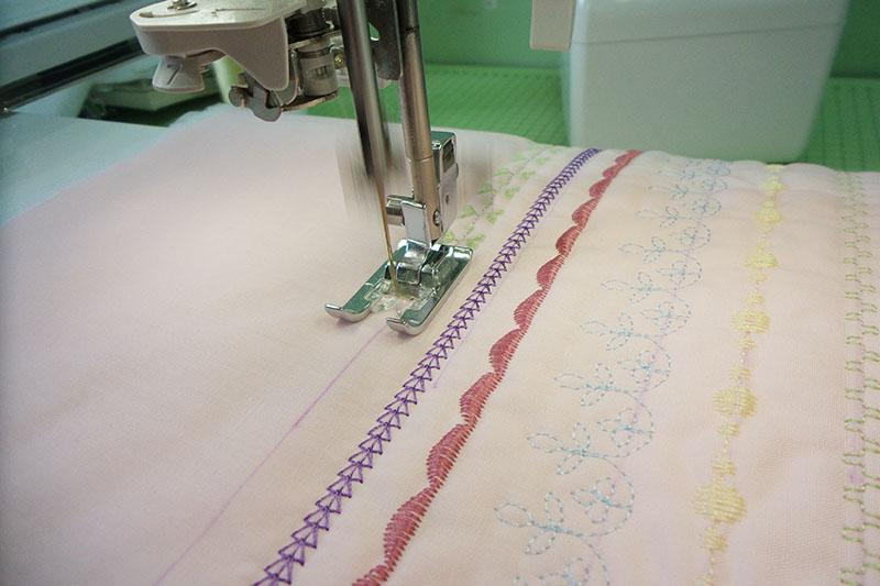 Rows of decorative stitches on pink fabric