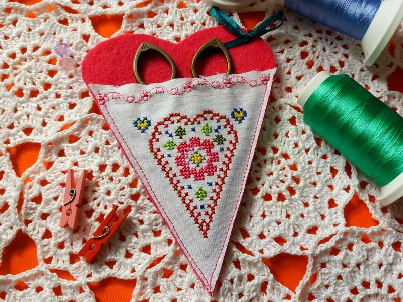 A heart-shaped scissors holder with embroidery