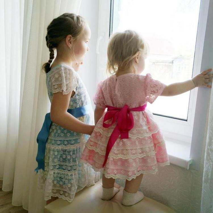 Two small girls in lacy dresses