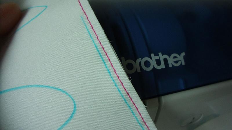 Row of pink straight stitched alonside blue line