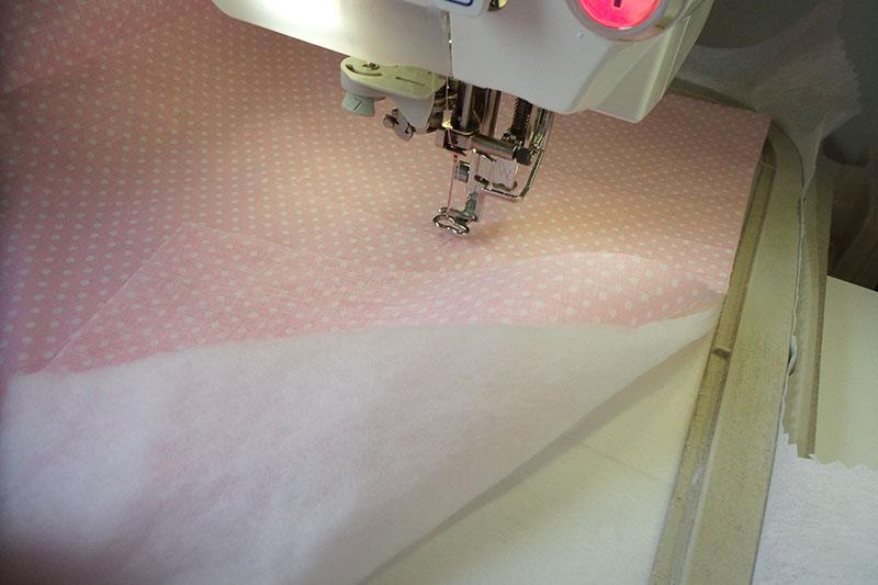Pink fabric with dots over polyester batting
