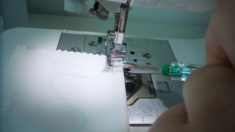 Pieced of white fabric under presser foot