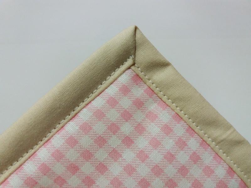 Corner of a pot holder with binding
