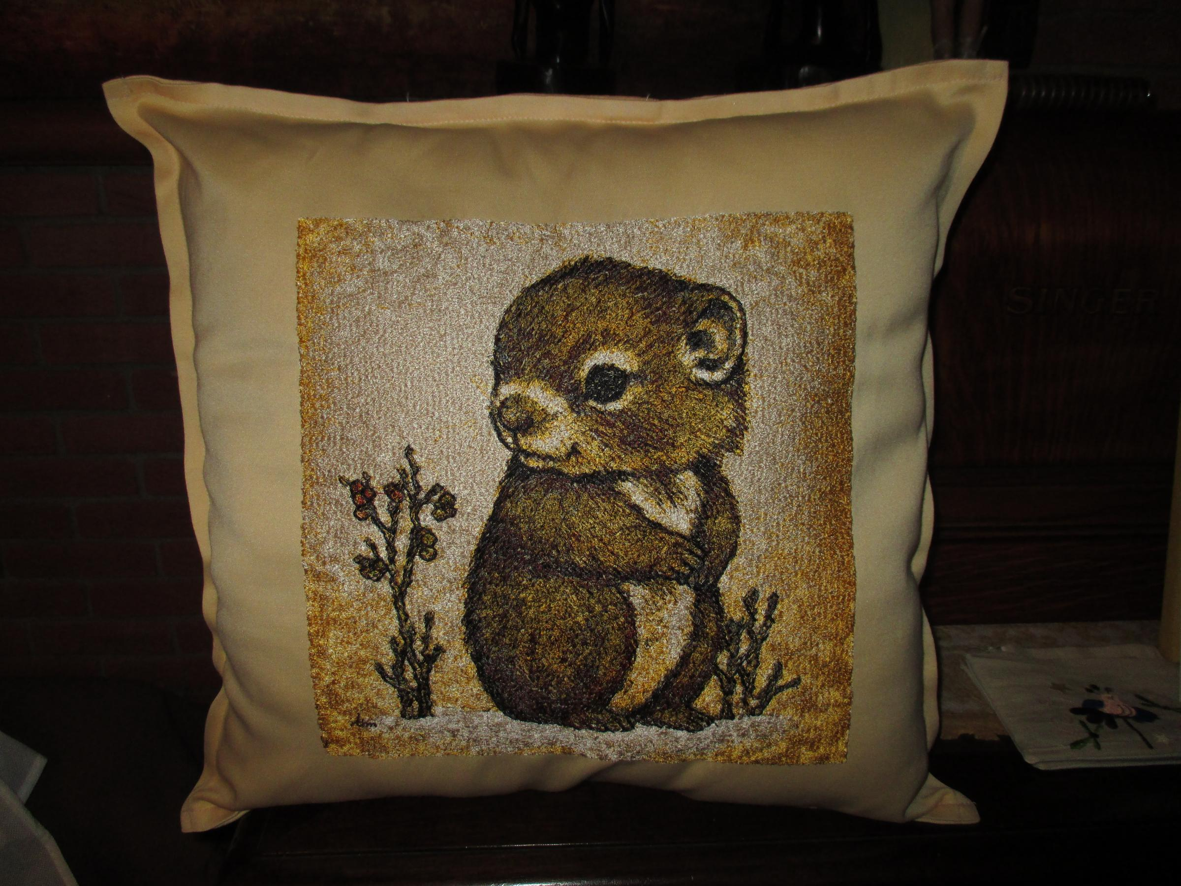 Embroidered pillow with hamster design